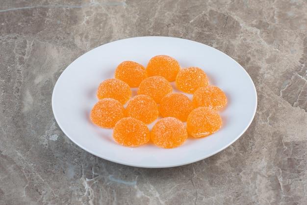 Deliziose caramelle di gelatina d'arancia sul piatto bianco.