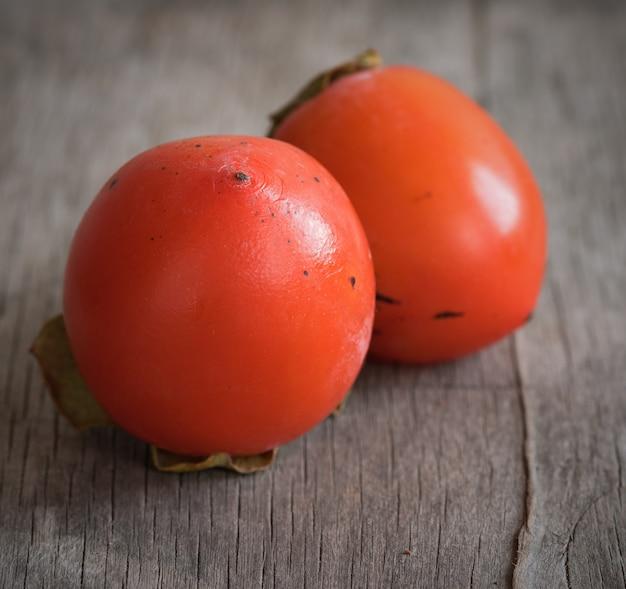木製のテーブルにおいしいオレンジ色の柿