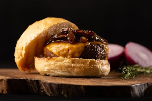 Вкусный бургер для гурманов. гамбургер с поджаренным и хрустящим хлебом, плавленый сыр на деревянном столе