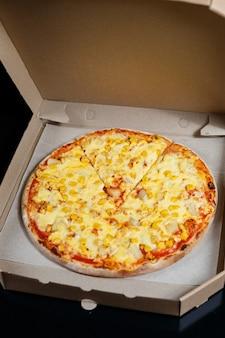 모짜렐라, 파마산 치즈, 치즈가 들어간 맛있는 오븐 구운 피자 요리를 골판지 상자에 담아 배달