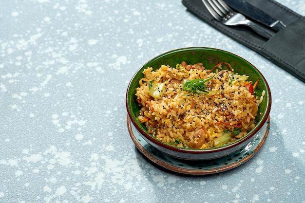 Вкусное паназиатское блюдо - рис вок с курицей, овощами и кисло-сладким соусом в зеленой миске на сером фоне. крупным планом, выборочный фокус
