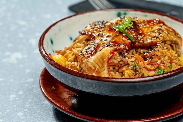 Вкусное паназиатское блюдо - рис вок с угрем, овощами и кисло-сладким соусом в зеленой миске на сером фоне