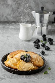 Delicious pancakes on plate with blackberry