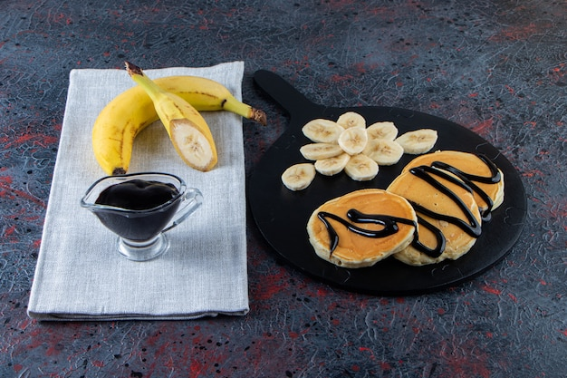 어두운 표면에 바나나와 초콜릿 토핑을 얹은 맛있는 팬케이크.