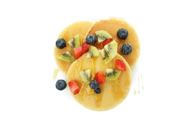 Вкусные блины с ягодами и медом, изолированные на белом фоне