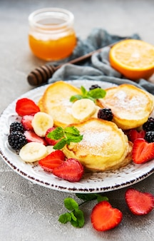 Delicious pancakes with berries on a concrete backrgound
