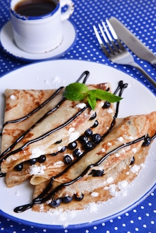 Delicious pancakes with blueberries on table close-up