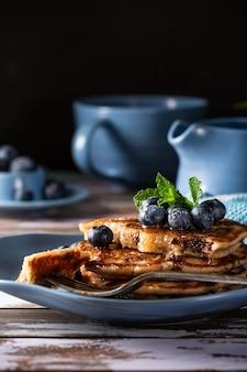 チョコレートドロップ、蜂蜜、ブルーベリーが入ったおいしいパンケーキ。コピースペースと健康的な朝食のコンセプト