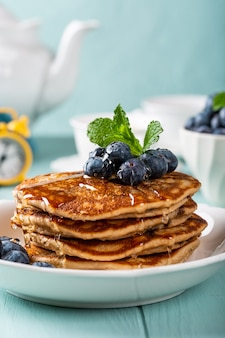 Delicious pancakes with chocolate drops, honey and blueberries. healthy breakfast concept with copy space