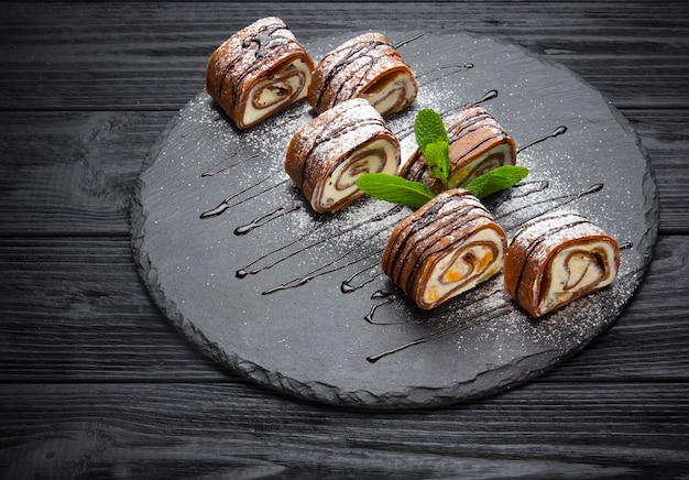Delicious pancakes with chocolate glaze,caramel and mint on wooden background
