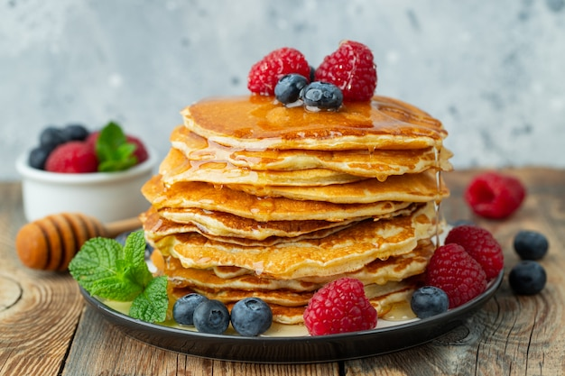 Delicious pancakes with fresh berries and honey