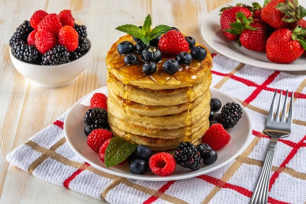 Delicious pancakes with fresh berries on white wooden table