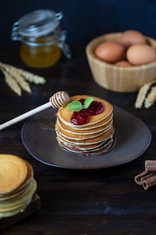 Delicious pancakes with jam and mint on a dark wooden table