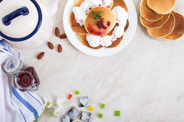 Вкусные блины с малиновым вареньем и взбитыми сливками на белой тарелке на кухонном столе. классический американский домашний завтрак. вид сверху
