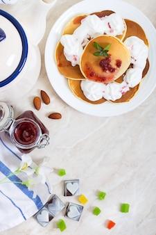 라즈베리 잼과 식탁에 하얀 접시에 휘 핑된 크림 맛있는 팬케이크. 고전적인 미국식 홈 메이드 조식. 상위 뷰