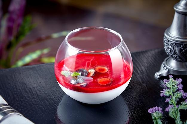 Вкусный панна котта (вареные сливки) итальянский десерт с клубникой и долива с клубничным соусом в небольшой прозрачный стакан на темном фоне. копировать пространство горизонтальный