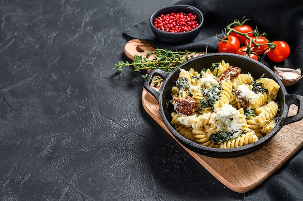 Delicious pasta fusilli dish with creamy spinach sauce and dried tomatoes.