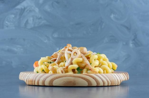나무 접시에 다진 닭고기와 함께 맛 있는 파스타.