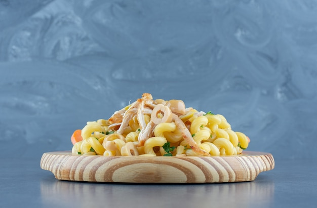 Delicious pasta with chopped chicken on wooden plate.