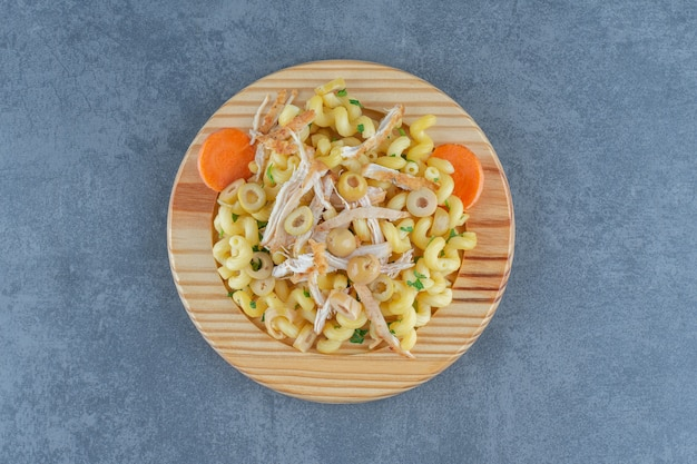 Deliziosa pasta con pollo tritato sul piatto di legno.