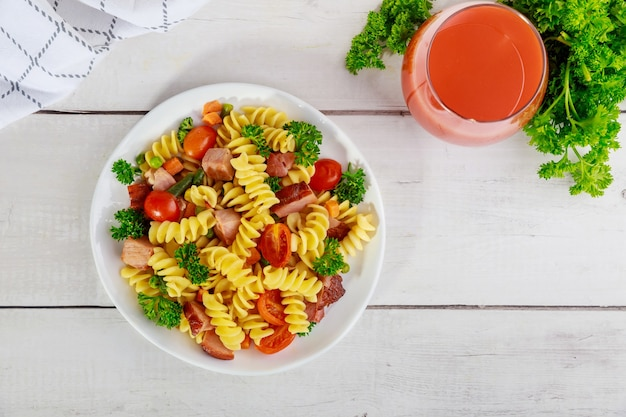 Delicious pasta with vegetables and cut ham. top view.