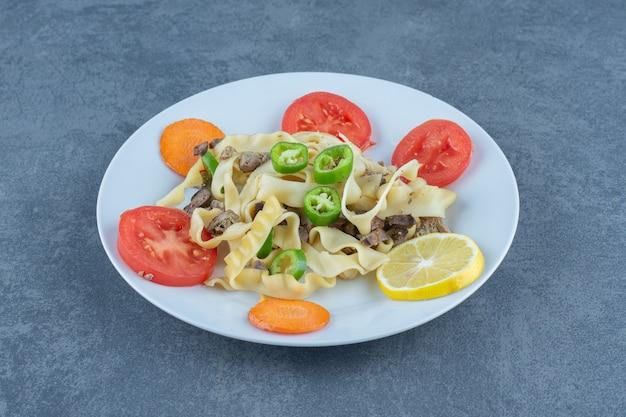 Вкусная паста с овощами на белой тарелке.
