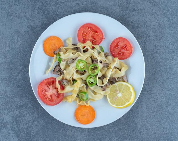 Deliziosa pasta con verdure sul piatto bianco.