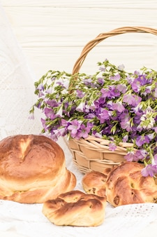 Delicious pastries (bread and rolls with raisins) and bouquet linen in wicker basket. retro style, vintage
