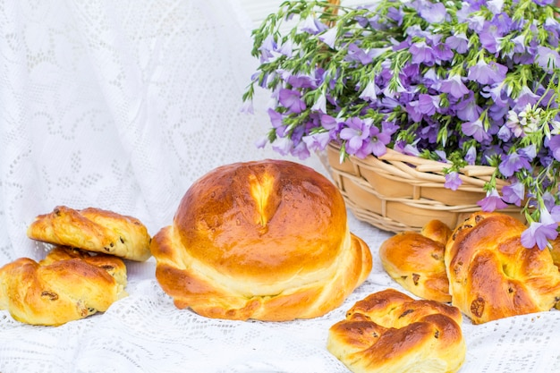 Delicious pastries (bread and rolls with raisins) and bouquet linen in wicker basket
