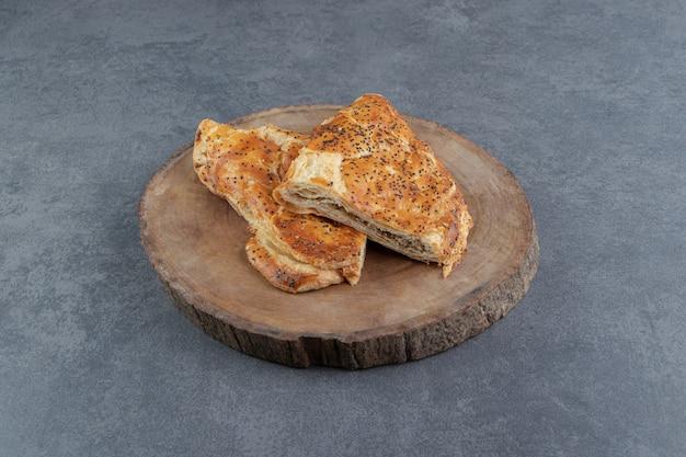 Deliziosi pasticcini ripieni di carne su pezzo di legno.