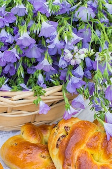 Delicious pastries (rolls with raisins) and bouquet linen in wicker basket