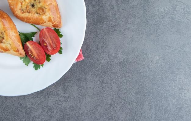 하얀 접시에 체리 토마토와 함께 맛있는 파이