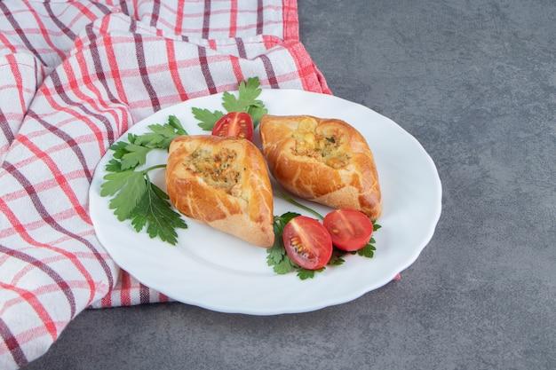 Deliziosi pasticcini con pomodorini in un piatto bianco