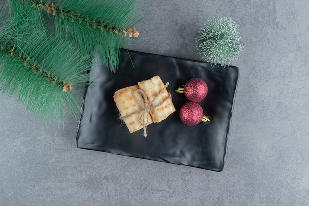 Delicious pastries with christmas balls on a dark plate