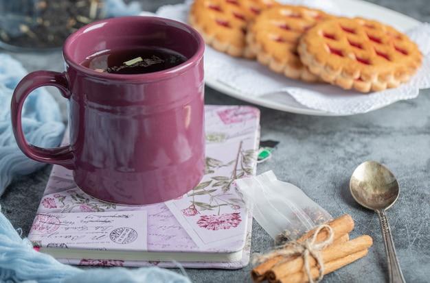 Deliziosi pasticcini con tazza di tè e bastoncini di cannella.