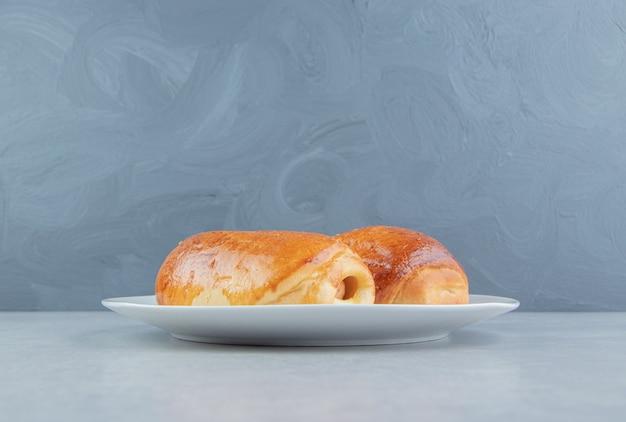 Deliziosi pasticcini con salsicce sul piatto bianco.