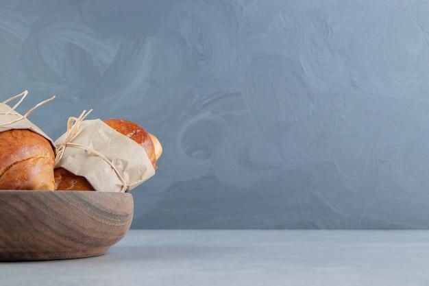 Salsicce deliziose della pasticceria in ciotola di legno.