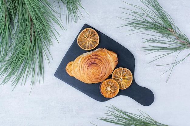 Вкусное тесто с сушеными дольками апельсина на черной доске. фото высокого качества