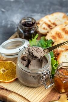 Вкусный паштет из утиной печени с кусочками белого хлеба на деревянной доске. закуски для гурманов, брускетта итальянских закусок ассорти