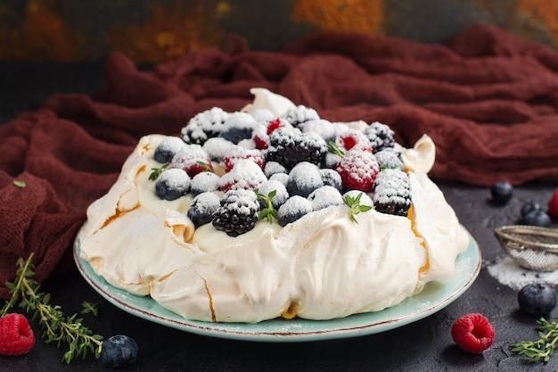 Delicious pavlova cake with cream and berries