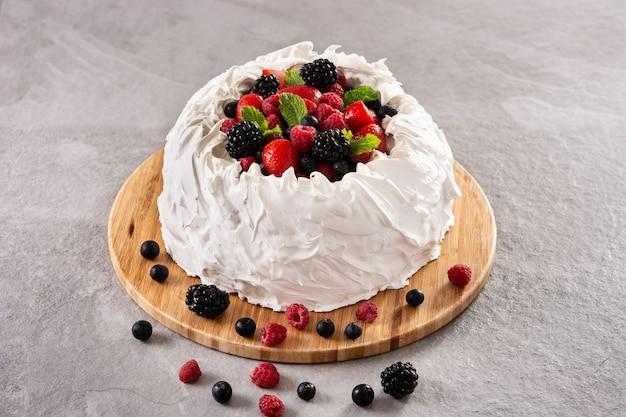 회색 돌에 머랭을 얹은 맛있는 파블로바 케이크와 신선한 딸기