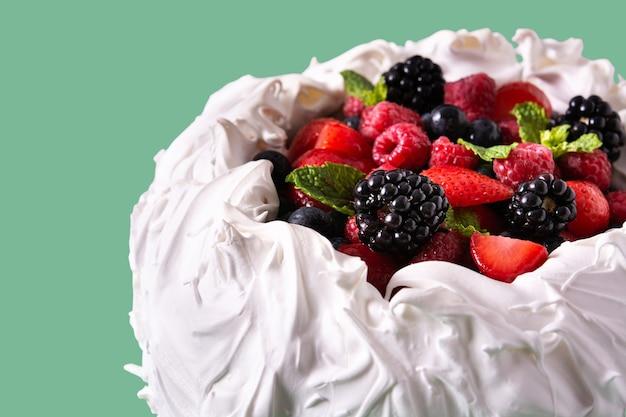 緑の背景にメレンゲをトッピングした新鮮なベリーとおいしいパブロバケーキ