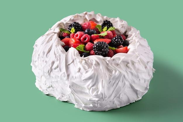 녹색 배경에 머랭을 얹고 신선한 딸기를 얹은 맛있는 파블로바 케이크