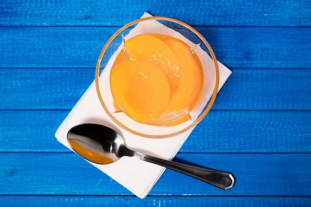 Buelの表面にあるガラスのボウルにシロップを入れたおいしい桃。健康食品のコンセプト。