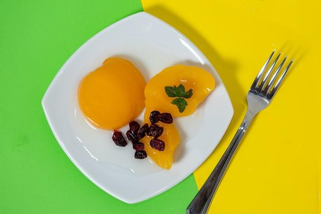 着色された表面のガラスのボウルといくつかのクランベリーのシロップのおいしい桃。健康食品のコンセプト。