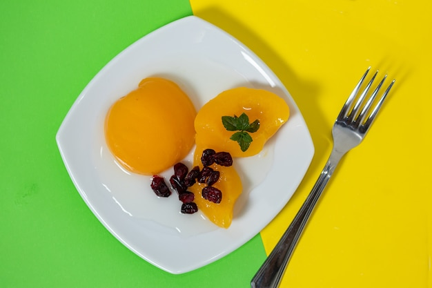 Delicious peaches in syrup in a glass bowl on a colored surface and some cranberries. concept healty food.