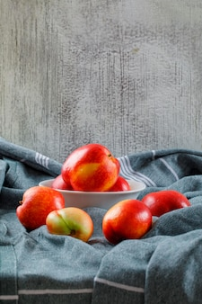 Delicious peaches in a white bowl side view on a clothing texture and grungy wall