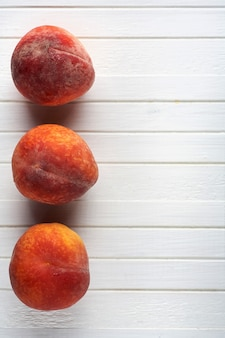 Delicious peaches on a white wooden background.