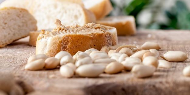 テーブルの上のおいしいピーナッツバターと白パン、パンとピーナッツの簡単な朝食を準備するための材料、ピーナッツペーストのローストピーナッツ