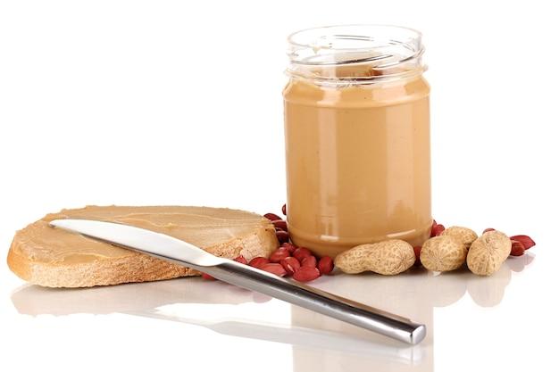 Вкусное арахисовое масло в банке с бутербродом на белом